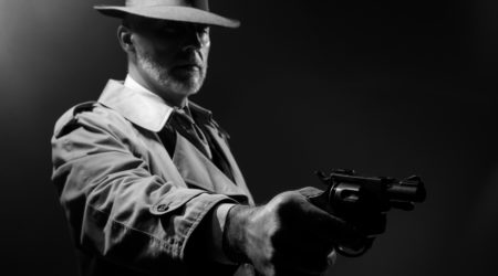 Undercover spy agent pointing a gun in the dark, 1950s noir film male character